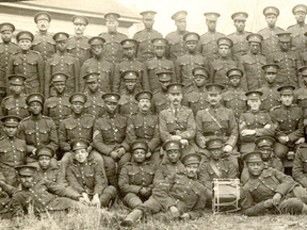 Group photo from 1916, soldiers standing and sitting in uniform, one man has a drum