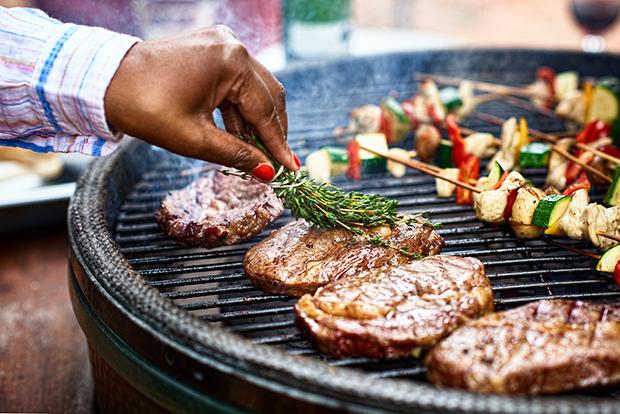 Hand visible, placing herbs on steak, other steaks and chicken/vegetable kabobs on grill