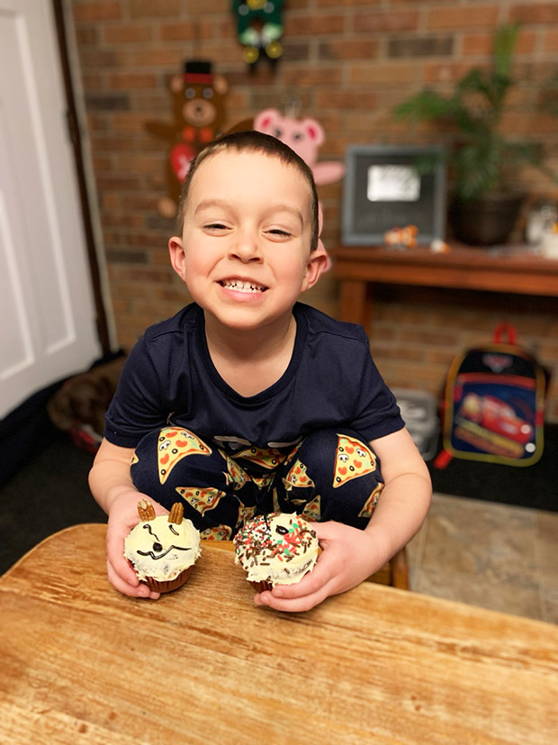Young, smiling boy sitting at counter holding a cupcake in each hadn