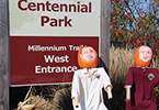 Two Pumpkin headed people in front of Centennial Park West entrance sign
