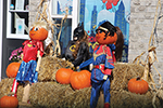 Pumpkin people dressed as superheroes in front of bales of hay and pumpkins