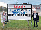 Dolly and Greg standing beside Kelsey's sign wishing them a Happy Anniversary
