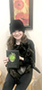 Gen wearing a black shirt and hat, holding her award and her black cat