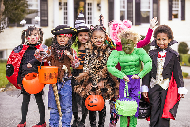 Seven children dressed up in various costumes for Halloween